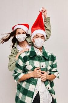 Un uomo con una camicia a quadri e una donna felice con una mascherina medica con un cappello festivo in testa
