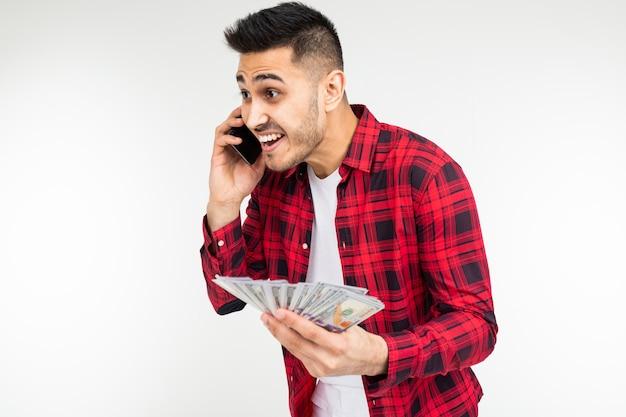 Un uomo in una camicia a quadri riferisce vincendo soldi in un casinò su uno sfondo bianco con spazio di copia