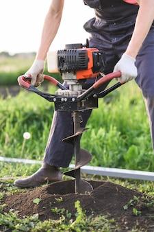 L'uomo pianta un albero, le mani con la pala scava il terreno, la natura, il concetto di ecologia