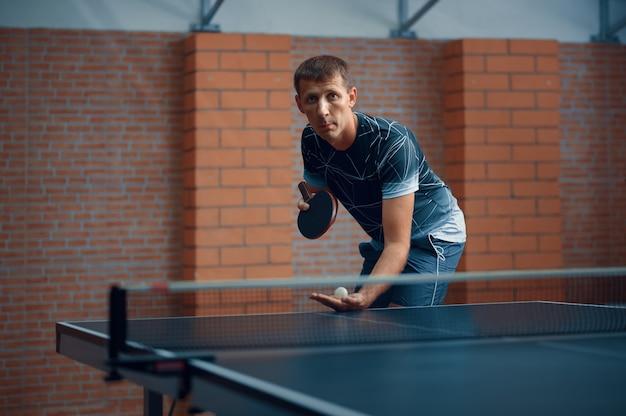 L'uomo gioca a ping pong, maschio giocatore di ping pong