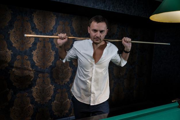 Un giocatore uomo sta in piedi a un tavolo da biliardo tenendo una stecca di legno con entrambe le mani e posizionandola sulle spalle dietro la testa