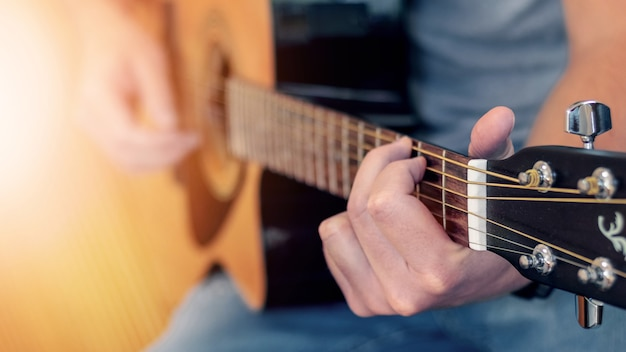 Uomo che suona la chitarra acustica, chitarra da vicino a una profondità di campo ridotta