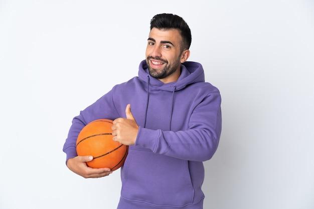 Uomo che gioca a basket sopra la parete bianca isolata che dà un pollice in alto gesto