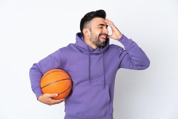 Uomo che gioca a basket sopra la parete bianca isolata che sorride molto