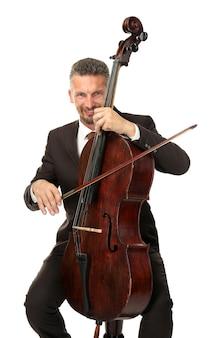 Uomo che suona il violoncello sul muro bianco