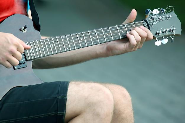 Uomo che suona una chitarra elettrica per strada