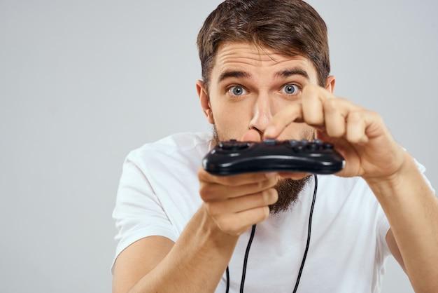 Uomo che gioca giochi divertenti con un joystick su sfondo chiaro.