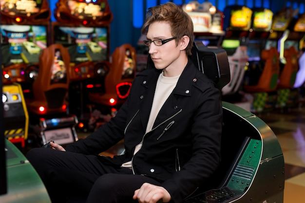 Uomo che gioca sulle attrazioni di slot machine nel centro commerciale