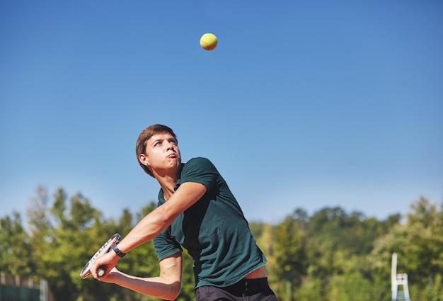 Un uomo che gioca a tennis sul campo in una bella giornata di sole Foto Premium