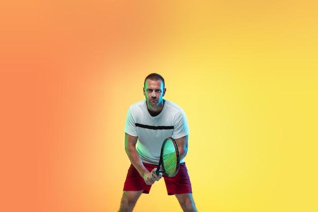 Uomo che gioca a tennis isolato su sfondo studio in luce al neon