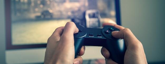 Uomo che gioca video gioco. mani che tengono il controller della console