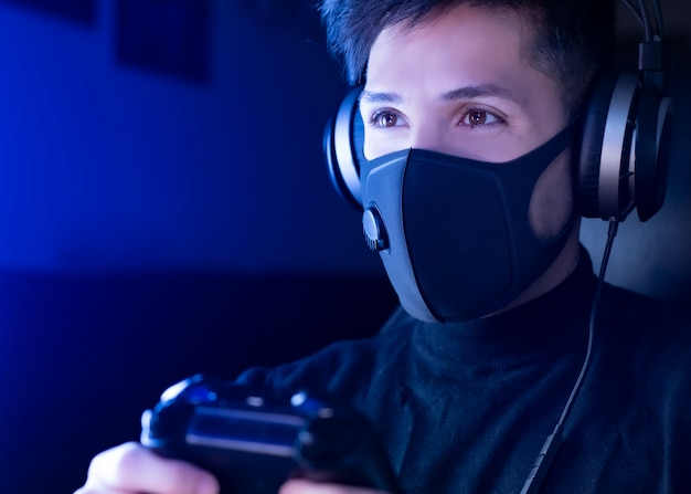 Equipaggi il gioco del video gioco che indossa una maschera chirurgica, con le cuffie. concetto: autoisolamento per coronavirus (covid-19) è tempo di giocare ai videogiochi.