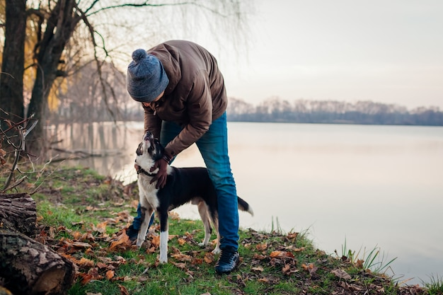 Equipaggi il gioco con il cane nel parco di autunno dal lago. animale domestico felice divertirsi camminando all'aperto