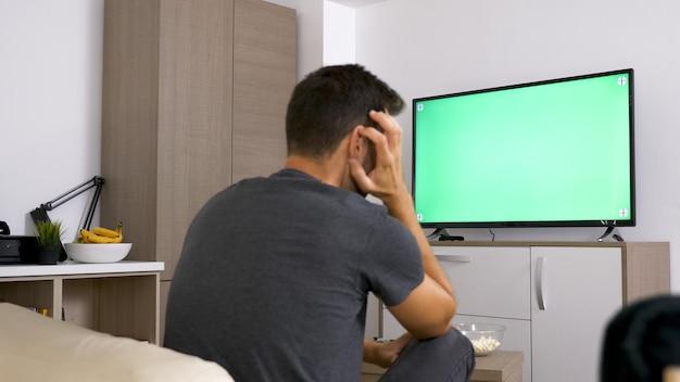 Uomo che gioca con il joystick mentre è seduto sul suo divano. tempo di relax