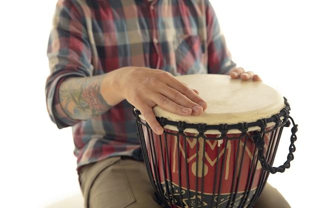 L'uomo suona le percussioni di darbuka di tamburo etnico, musicista ravvicinato isolato su sfondo bianco per studio. mani maschili che toccano djembe, bongo a ritmo. strumenti musicali fatti a mano, suono della cultura mondiale.