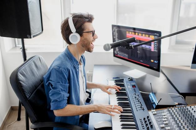 L'uomo suona il pianoforte e canta in studio