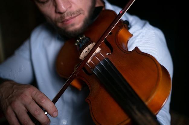 Un uomo suona un violino in primo piano.