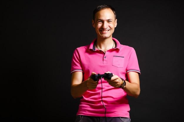 Un uomo gioca con un joystick a casa su uno sfondo nero