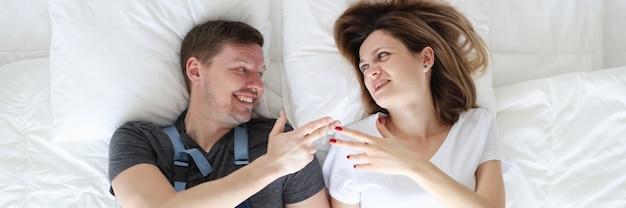 Idraulico uomo e donna sdraiata a letto con sigaretta vista dall'alto concetto di infedeltà femminile
