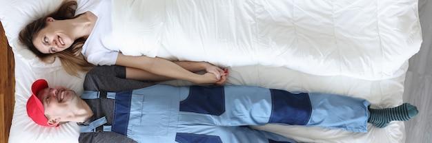 Idraulico uomo e donna sdraiati sotto la coperta vista dall'alto marito per ora concept