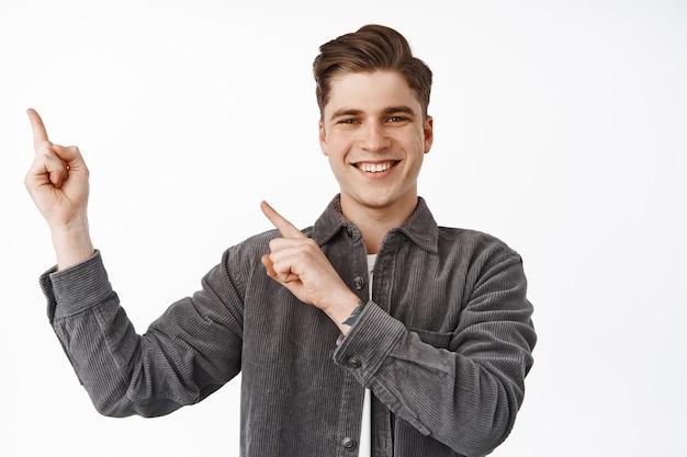 Uomo che punta le dita nell'angolo in alto a sinistra, sorride felice e soddisfatto su bianco