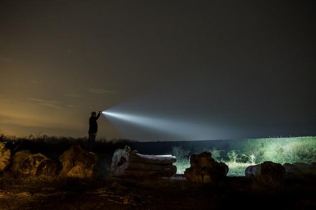 Uomo che punta la torcia elettrica alla foresta di notte