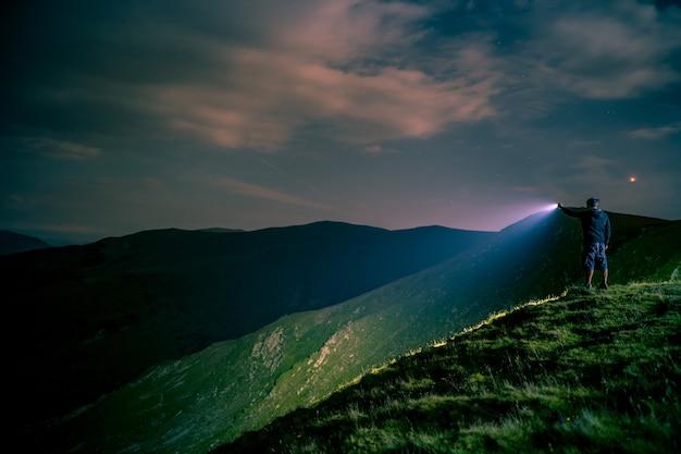 Uomo che punta la torcia elettrica alle montagne di notte.