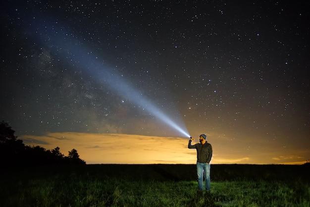Uomo che punta la torcia al cielo di notte.