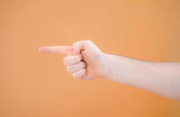 L'uomo indica con l'indice qualcosa o fa una scelta su uno sfondo arancione. avvicinamento