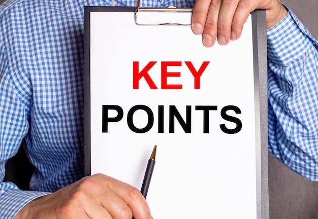 L'uomo indica con una penna il testo punti chiave su un foglio bianco.