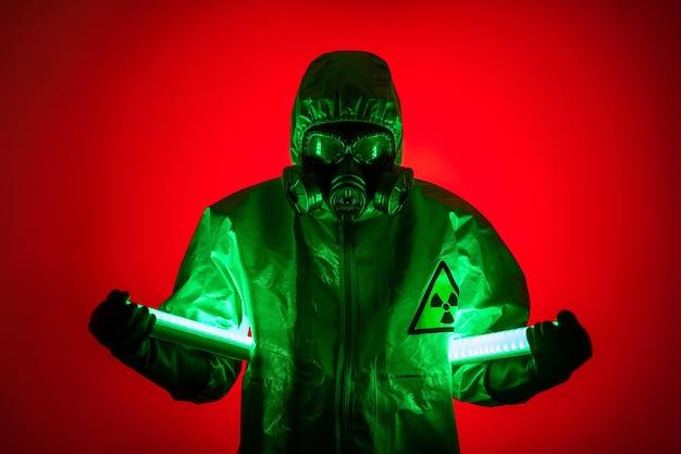 Un uomo posa in una tuta protettiva gialla con un cappuccio in testa, con una maschera antigas protettiva, in posa mentre in piedi su uno sfondo rosso, tenendo in mano lampade all'uranio. lampade a diodi.