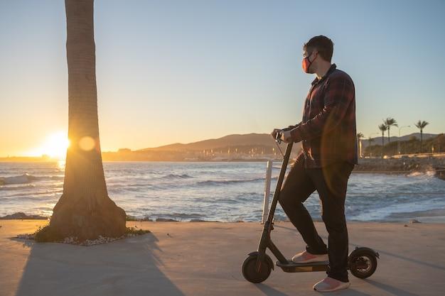 Uomo in posa sul suo scooter elettrico al tramonto sul mare a palma de mallorca, spagna.