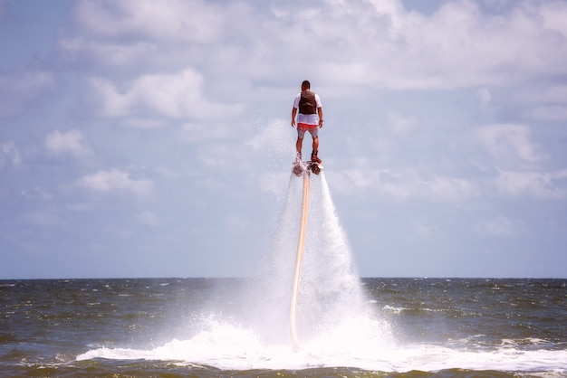 Uomo che propone al flyboard estremo dell'acqua.