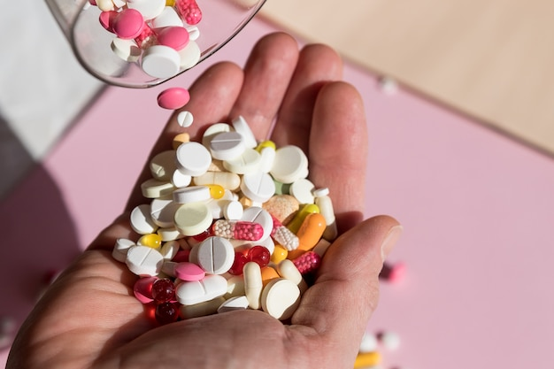 Uomo versare le capsule da una bottiglia di pillola, tenendo in mano le pillole. overdose di farmaci. molte pillole si sono rovesciate sul tavolo. tentativo di suicidio. crisi economica e problemi di medicina. pandemia virale.