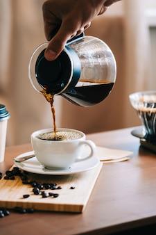 Uomo che versa il caffè in una tazza, metodo alternativo per la preparazione del caffè, utilizzando il gocciolatore e il filtro di carta.