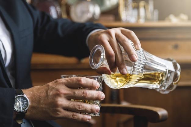 Uomo che versa whisky costoso nel bicchiere di cristallo