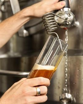 L'uomo versando, riempiendo il bicchiere di birra, boccale dalla botte