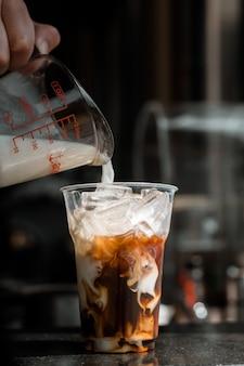 Uomo che versa il latte in un bicchiere di caffè freddo