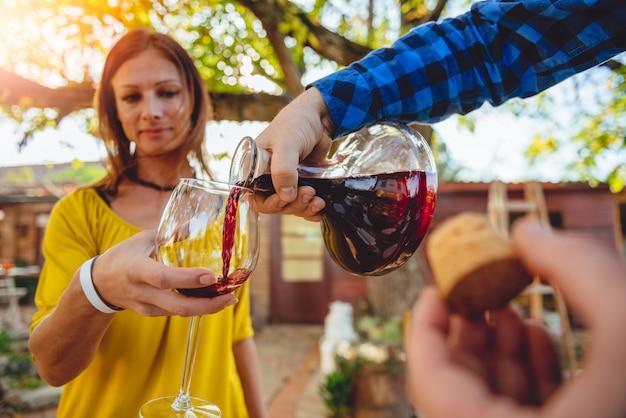 Uomo che versa vino rosso dal decantatore