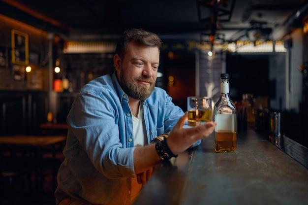 L'uomo versa l'alcol al bancone del bar. una persona di sesso maschile che riposa in un pub, emozioni umane e attività ricreative