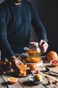 Un uomo versa il tè agli agrumi su un tavolo di legno. bevanda salutare, stile vintage. prodotti vegani ed ecologici.