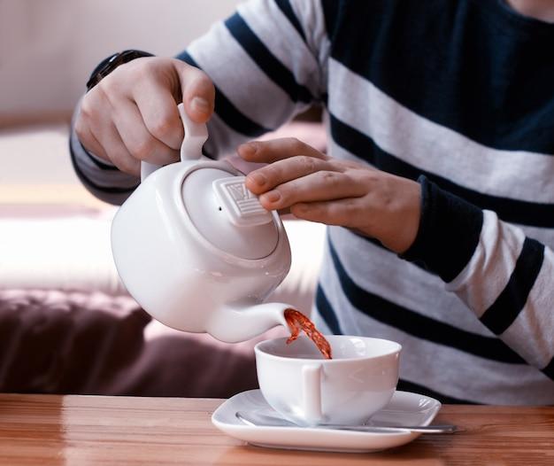 L'uomo versa il tè alla frutta dalla teiera nella tazza bianca sul tavolo di legno