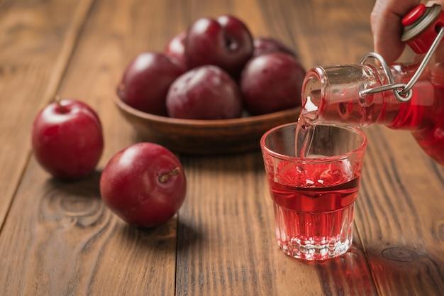 Un uomo versa un bicchiere di liquore alla prugna su un tavolo di legno. bevanda alcolica fatta in casa a base di prugne frutti di bosco.