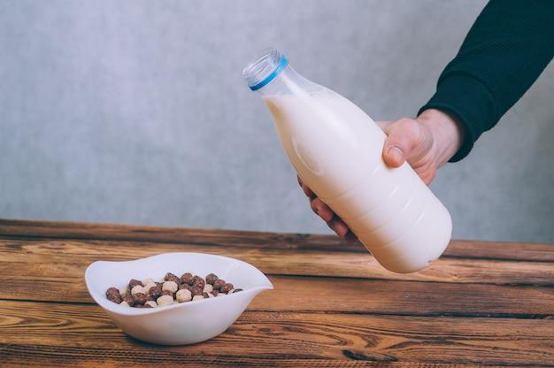 Un uomo versa il latte in cornflakes su un legno.
