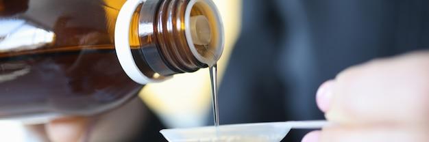 L'uomo versa lo sciroppo dolce dalla bottiglia nel concetto delle medicine liquide del cucchiaio