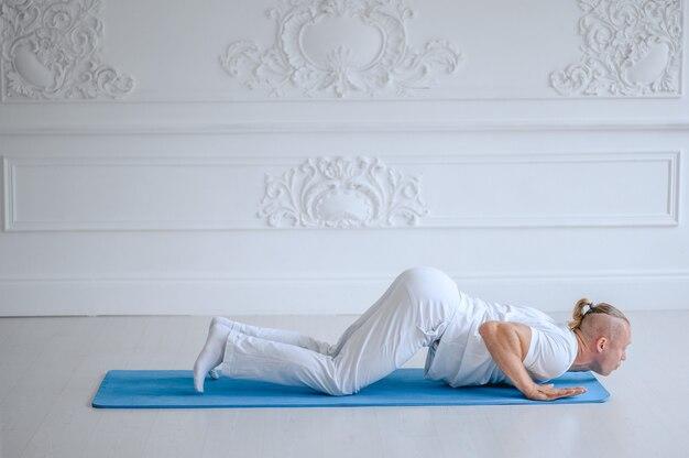 Uomo che pratica yoga avanzato contro un muro bianco. uomo che fa yoga