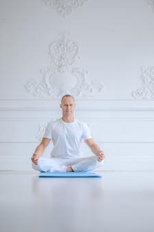 Equipaggi la pratica dell'yoga avanzata contro una parete bianca