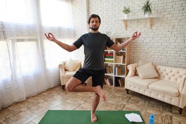 Uomo che pratica yoga avanzato a casa. esercizi sportivi.