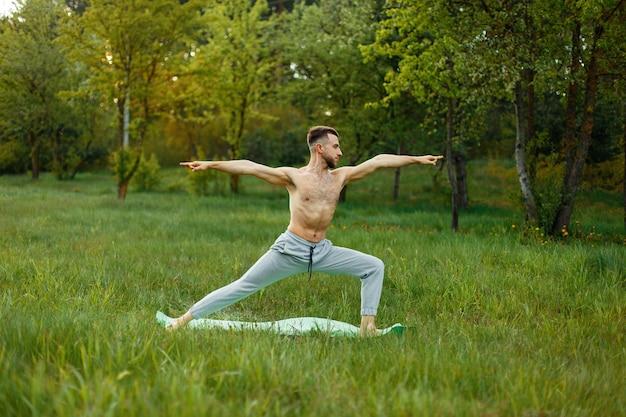 Uomo a praticare yoga in giardino sull'erba