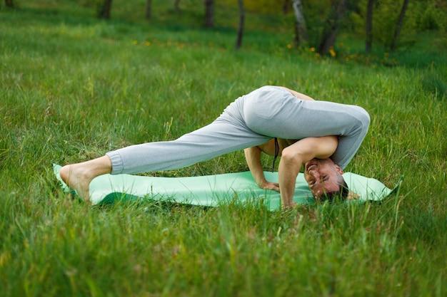 Uomo a praticare yoga nel verde del parco in una giornata estiva